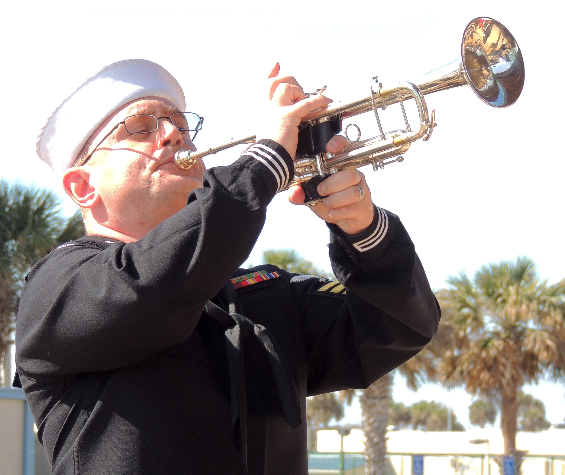 "A United States Navy sailor plays the ""Last Post"" during the ceremony commemorating the life of Lieutenant Barry Troy whose Banshee fighter jet crashed off the coast of Florida on February 25, 1958. PHOTO: Joanna Calder, RCAF public affairs"