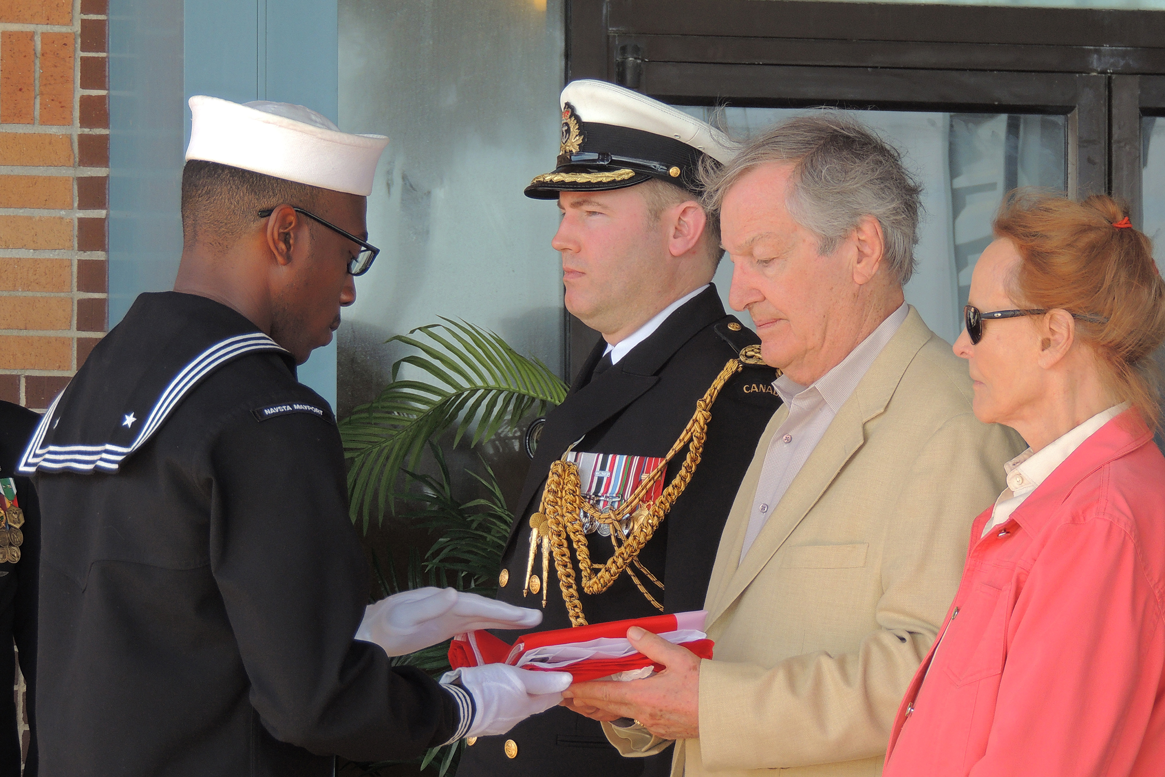 A United States Navy sailor presents Mr. Troy with a Canadian flag that flew at the Embassy of Canada on February 25, 2018, 60 years to the day since fighter pilot Lieutenant Barry Troy was lost off the coast of Florida near U.S. Naval Station Mayport. With Mr. Troy are Captain (Navy) Kristjan Monaghan, the Canadian naval attaché at the Embassy of Canada in Washington, and Mrs. Pauline Troy. PHOTO: Joanna Calder, RCAF Public Affairs