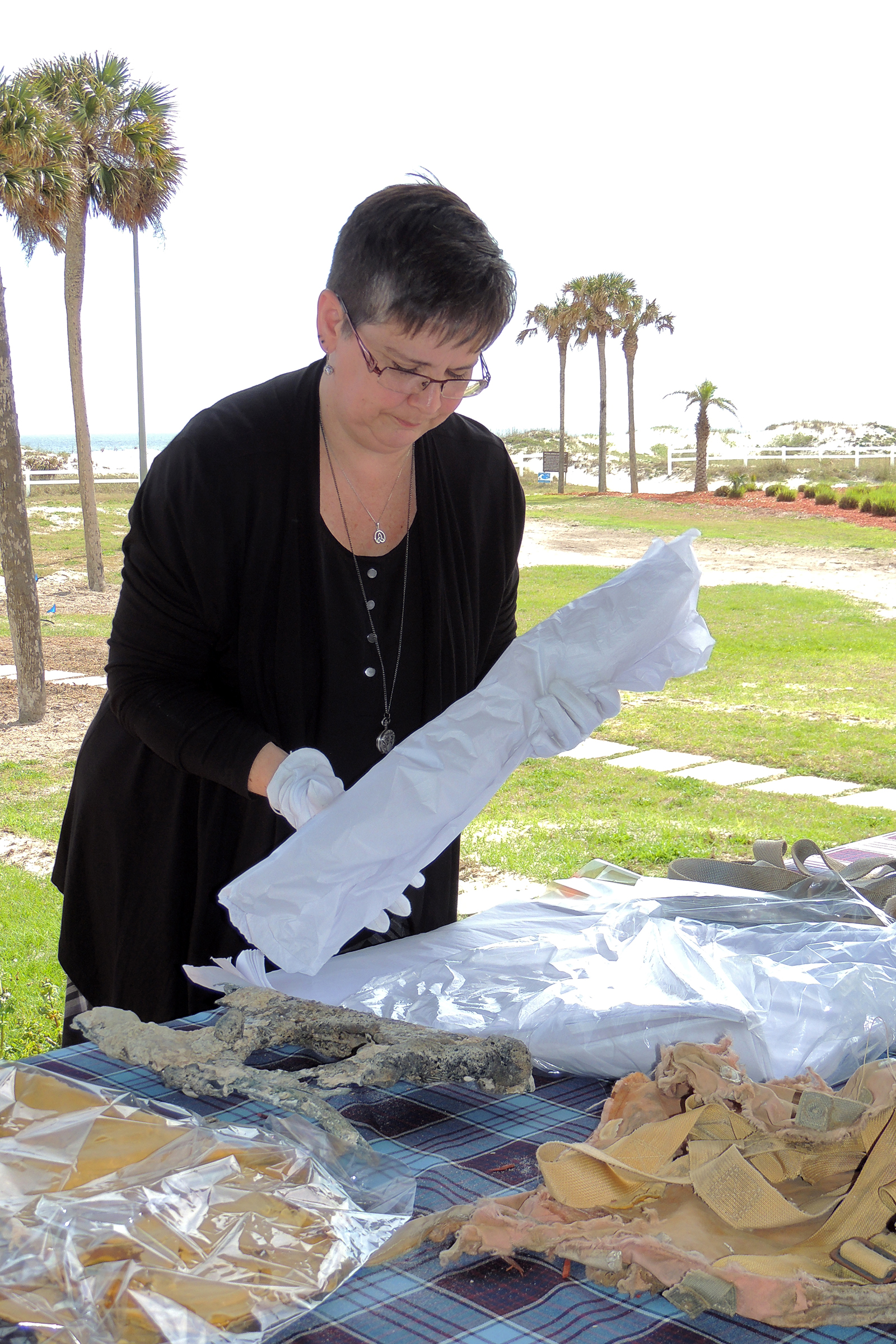 After six decades of being in the waters of the Atlantic Ocean or buried in the sands of a Florida beach, the artifacts relating to Lieutenant Barry Troy, who crashed off the coast of Florida on February 25, 1958, are now receiving the white glove treatment. Ms Christine Hines, curator of the Shearwater Aviation Museum in Nova Scotia, packs the artifacts for transport to Canada. PHOTO: Joanna Calder, RCAF public affairs