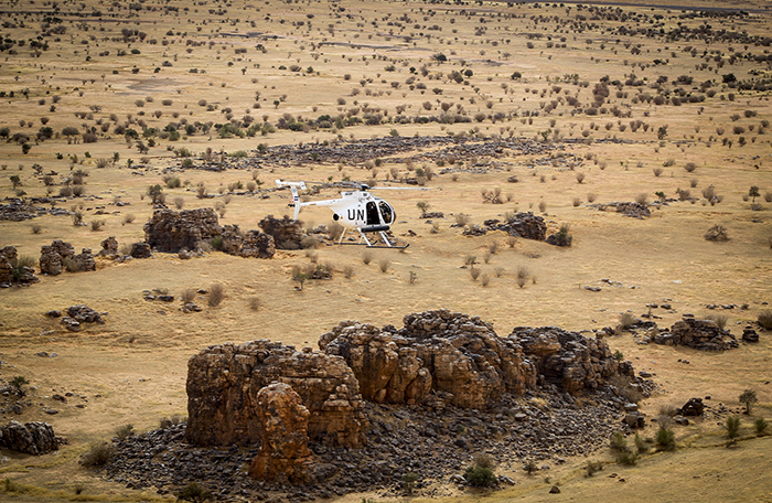 A helicopter flies over an arid desert landscape.