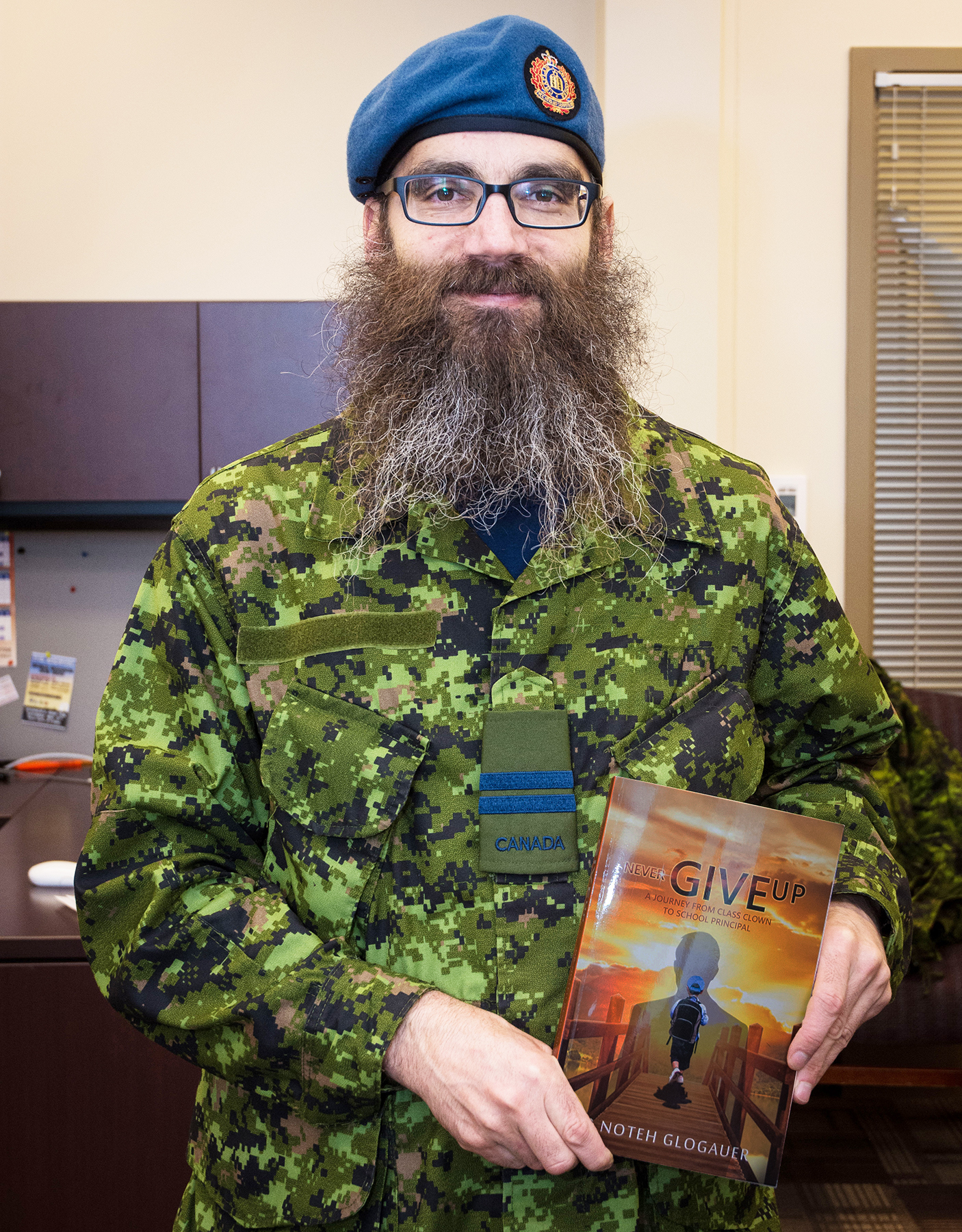 A bearded man wearing a military uniform holds a book.