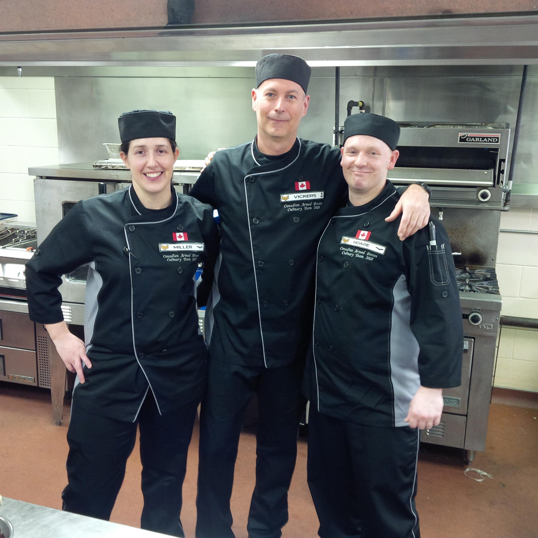 Two men and a woman in black chef's clothing stand in a line in a kitchen with their arms around each other's shoulders.