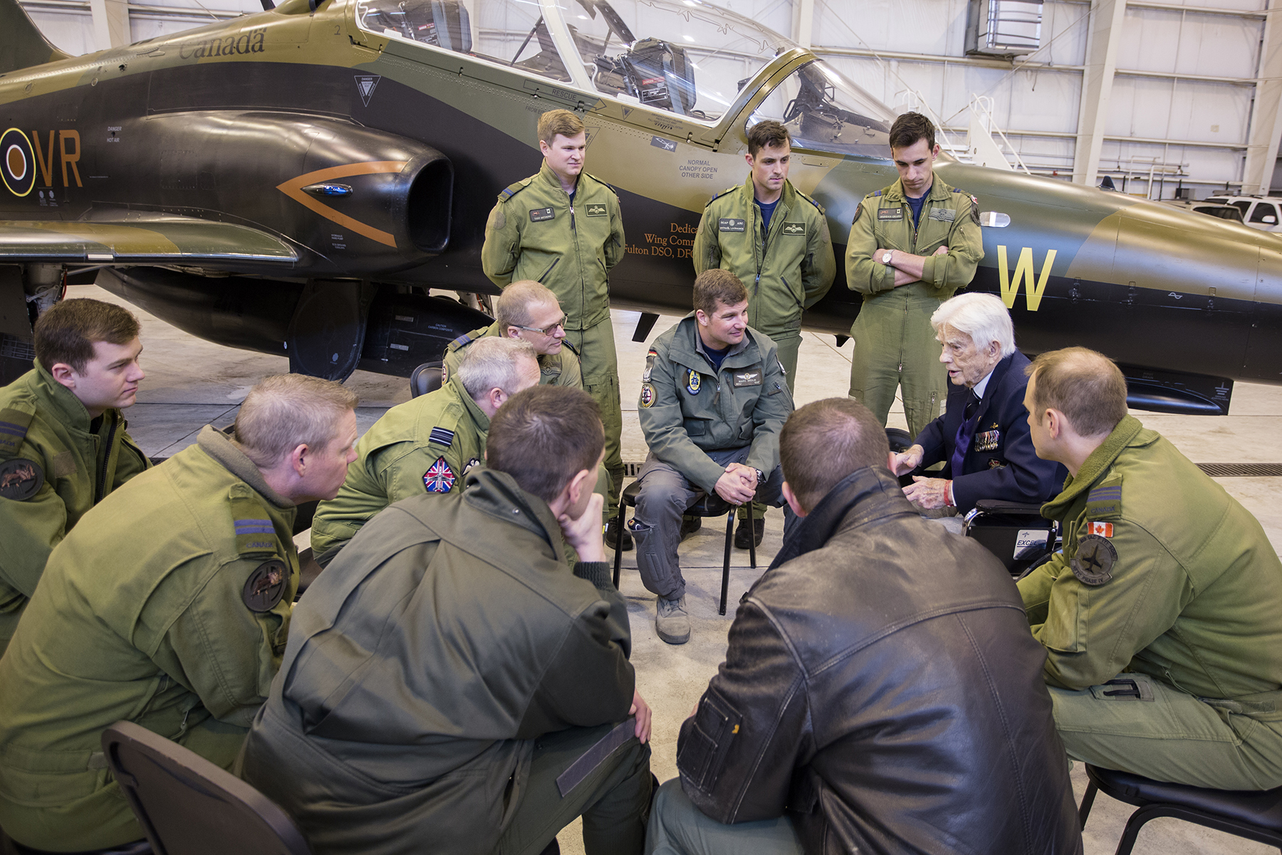 A white-haired man in a suit sits facing a group of men in olive green uniforms or casual clothing beside a small aircraft.