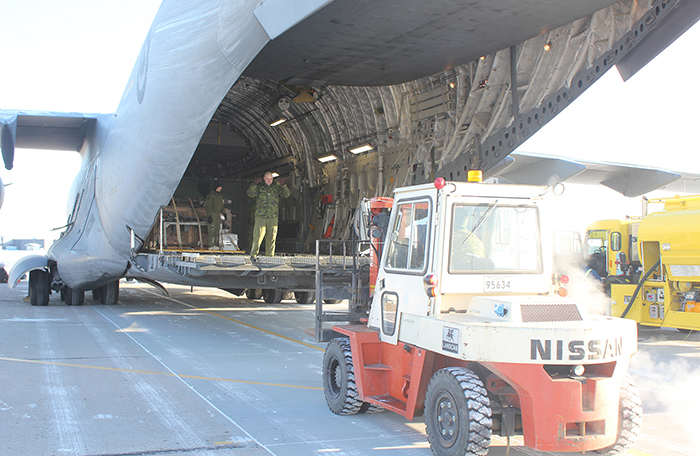 slide - A front-end loader positions itself behind the open cargo ramp of a large aircraft.