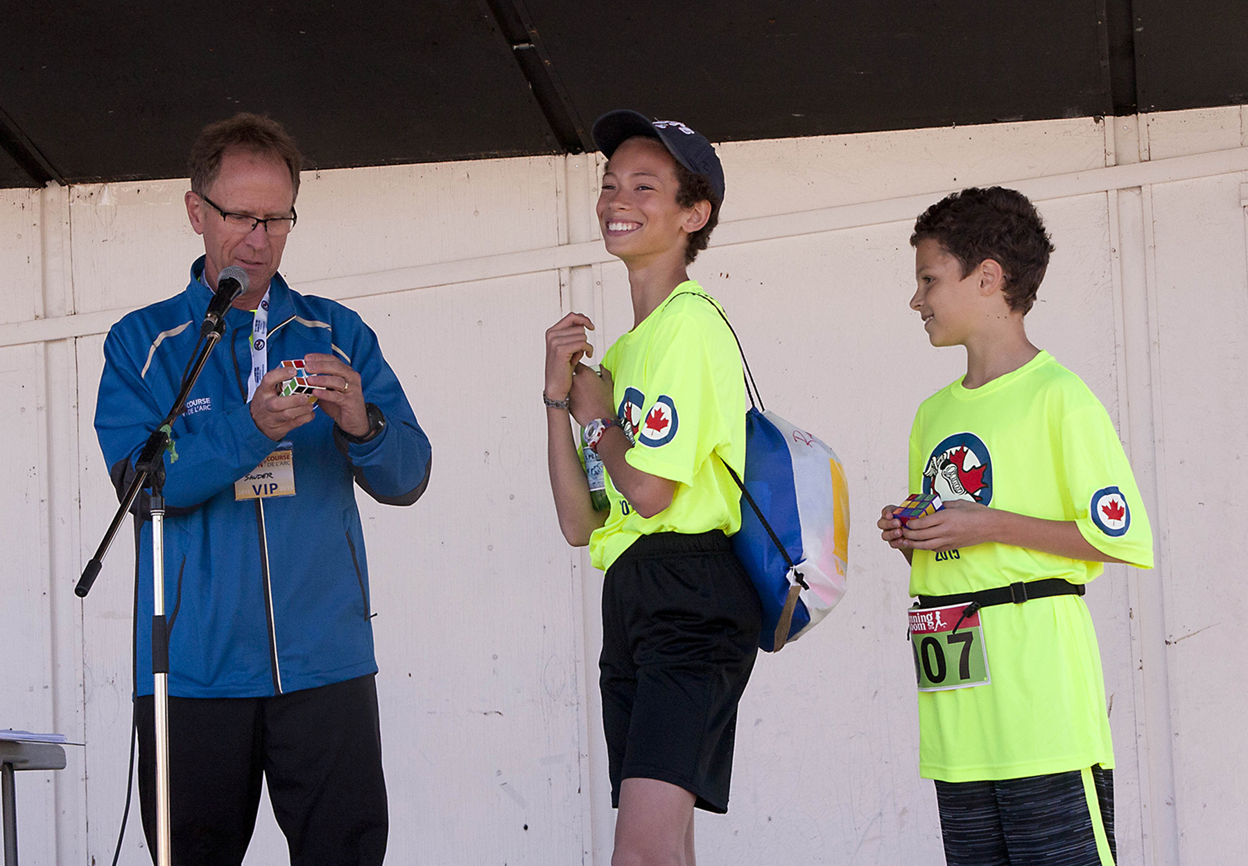 And then there are runners for whom the RCAF Run is not quite challenging enough: Winnipeg students Kingston Harding (Grade 6) and Alex Sala (Grade 5), from Winnipeg's École Dieppe, who completed the 2015 Run while solving Rubik's Cubes, stump a (stationary) Run VIP with a Cube. PHOTO: Voxair