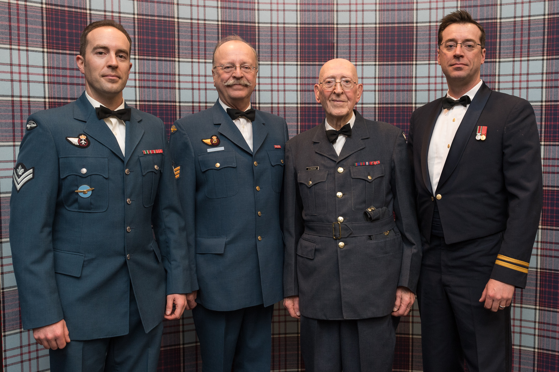 Four men of varying ages, wearing uniforms with bow ties, stand in a line in front of a tartan backdrop.