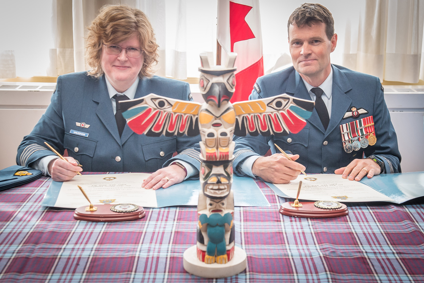 A woman and a man sit a tartan-covered table with documents and a miniature totem pole in front of them and a flag in the background.