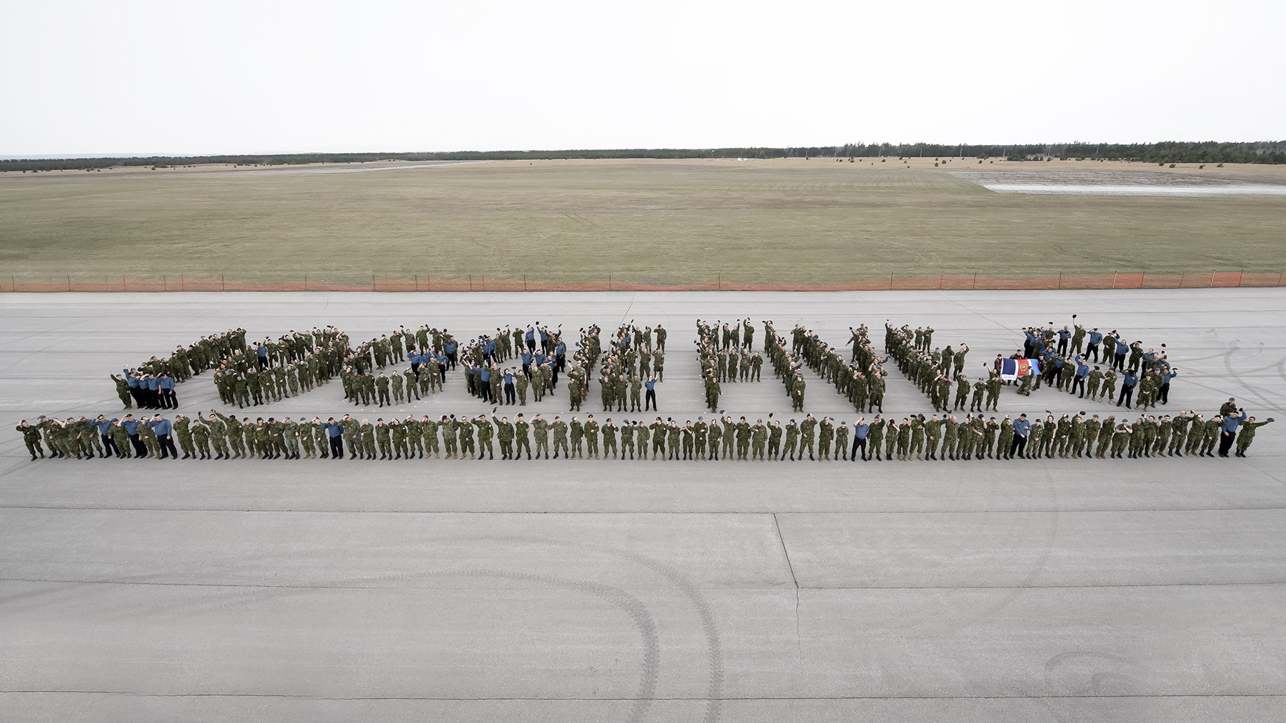 "Hundreds of uniformed people arrange themselves on tarmac to form the words ""LOGGIE-FIVE-0"""