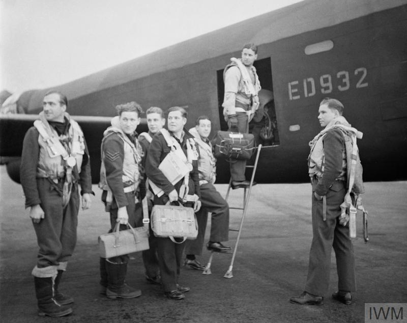 Several men wearing flying uniforms and life vests in front of a large aircraft.
