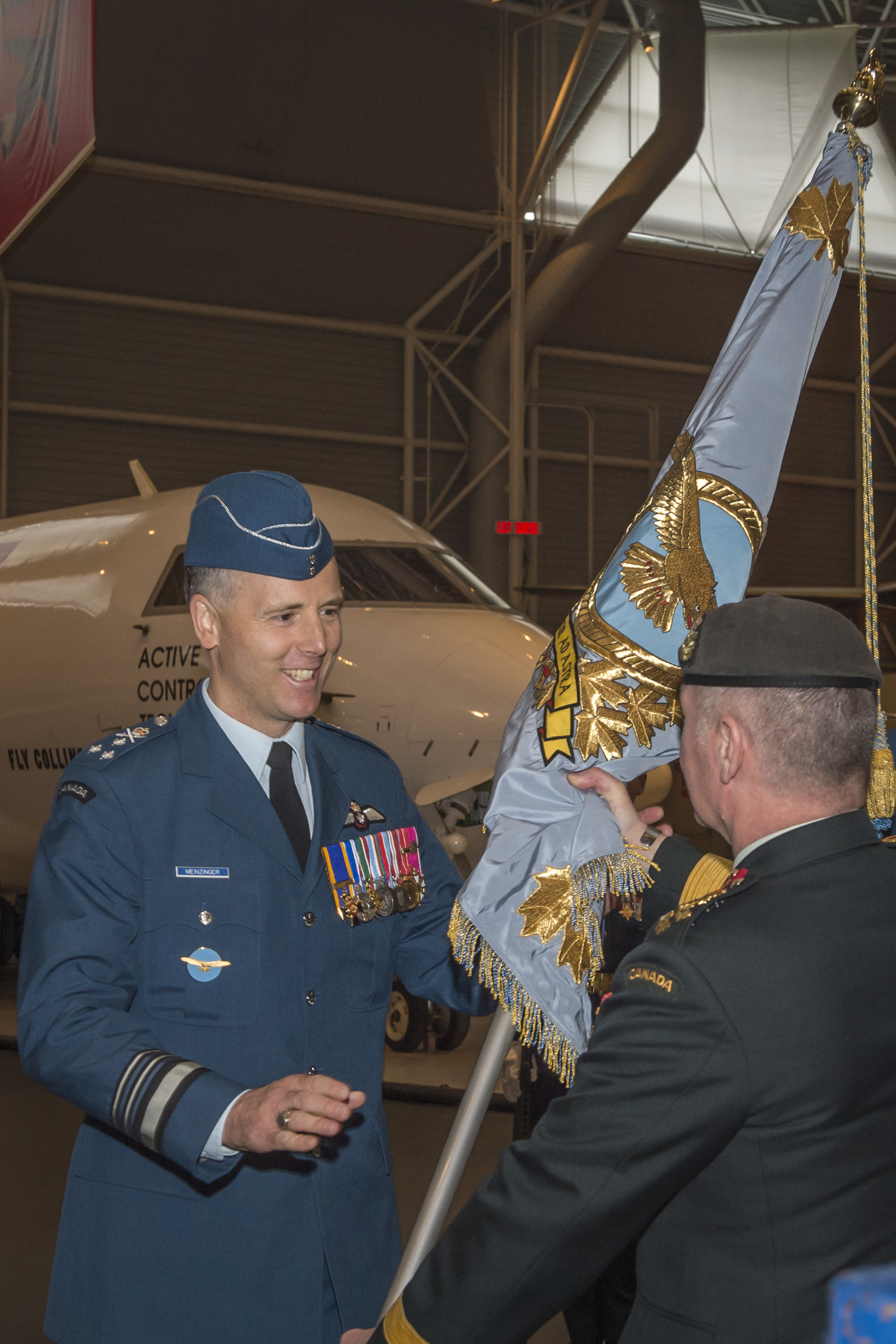 General Jonathan Vance, Chief of the Defence Staff, passes the Royal Canadian Air Force Colour (a special, consecrated flag) to the new commander of the RCAF, Lieutenant-General Al Meinzinger, thereby symbolizing the passing of command to Lieutenant-General Meinzinger. PHOTO: Corporal Alana Morin, FA03-2018-0040-001