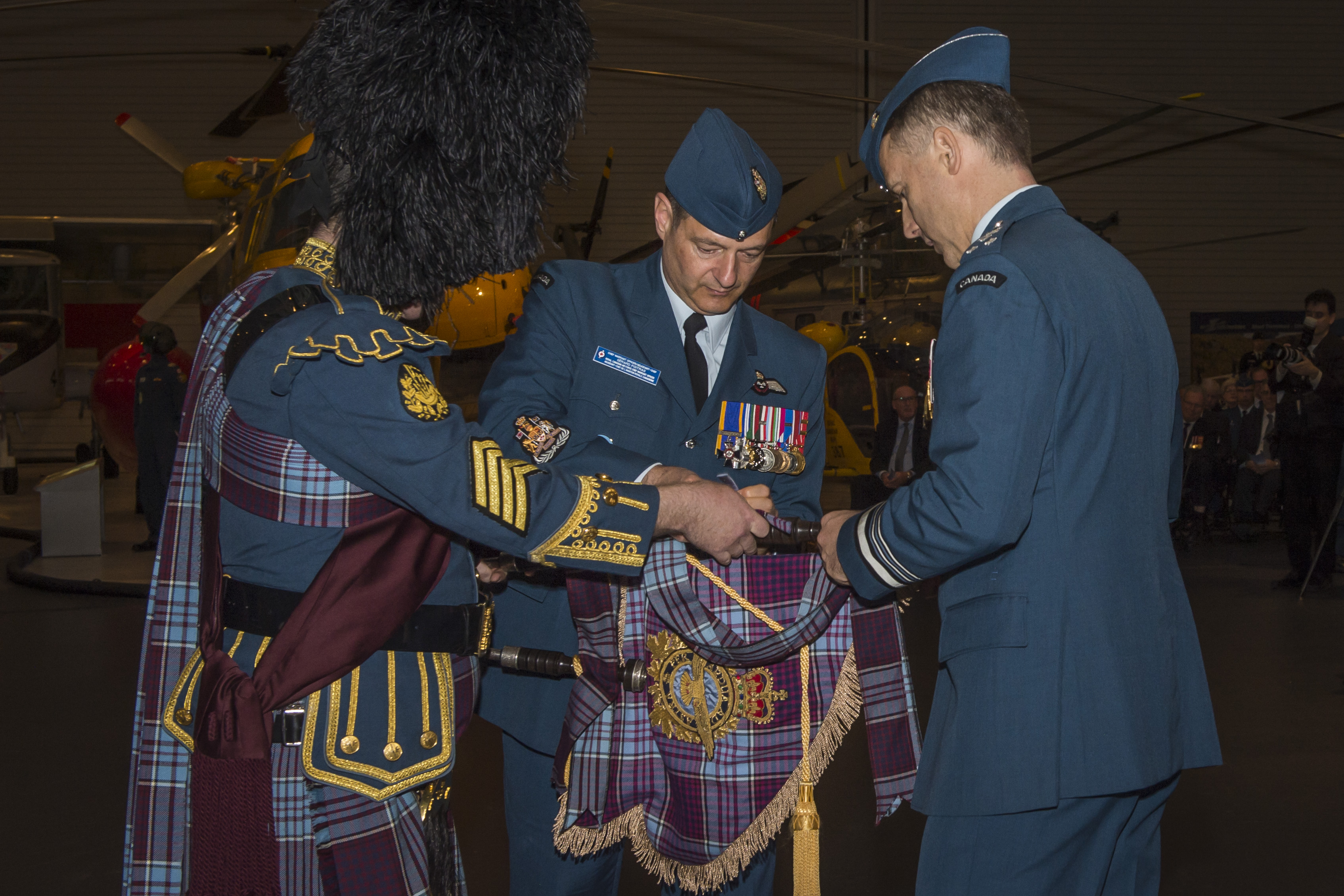 The RCAF command chief warrant officer, Chief Warrant Officer Gérard Poitras (centre), assists the new commander, Lieutenant-General Al Meinzinger, in affixing the new commander's pipe banner to the bass drone of Sergeant Malcolm Odell's bagpipes. Sergeant Odell is the pipe major of the RCAF Pipes and Drums. PHOTO: Corporal Alana Morin, FA03-2018-0040-005