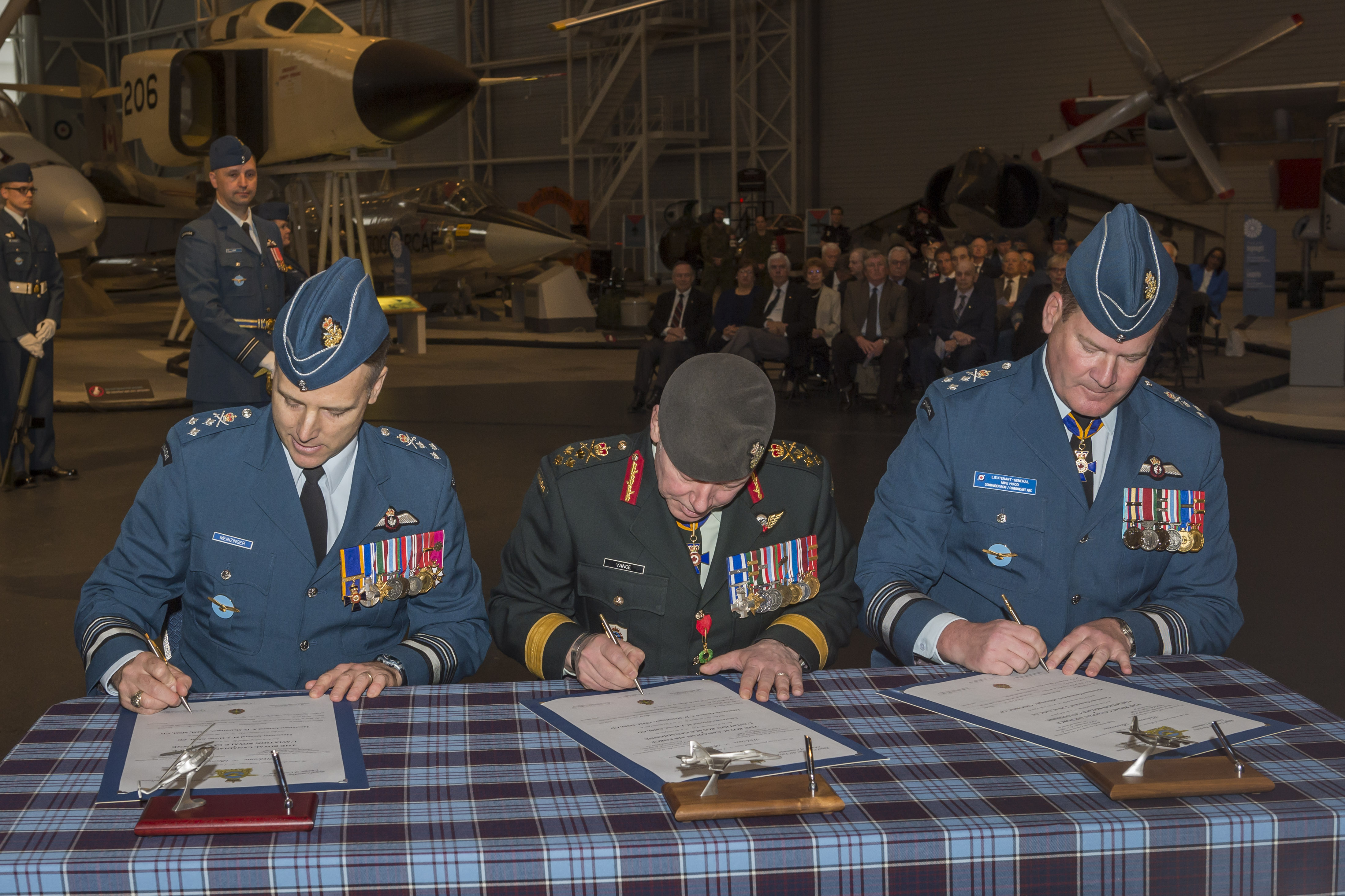 Making it official. From left, the incoming commander of the RCAF, Lieutenant-General Al Meinzinger; the chief of the defence staff, General Jonathan Vance; and the outgoing commander of the RCAF, Lieutenant-General Mike Hood, sign the change of command documents. PHOTO: Corporal Alana Morin, FA03-2018-0040-041