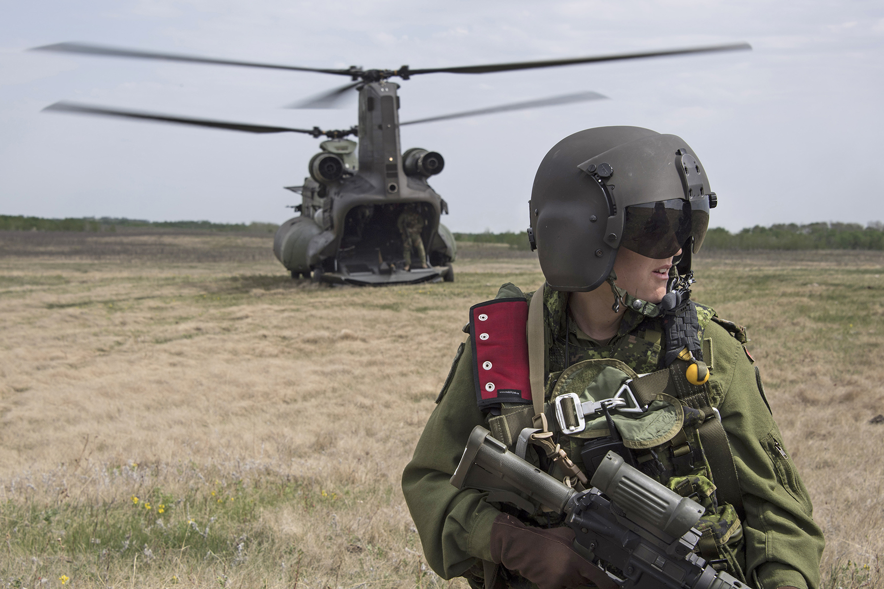 A person wearing a helmet with closed visor and a military uniform holds a rifle. In the background is a large, two-rotored helicopter.