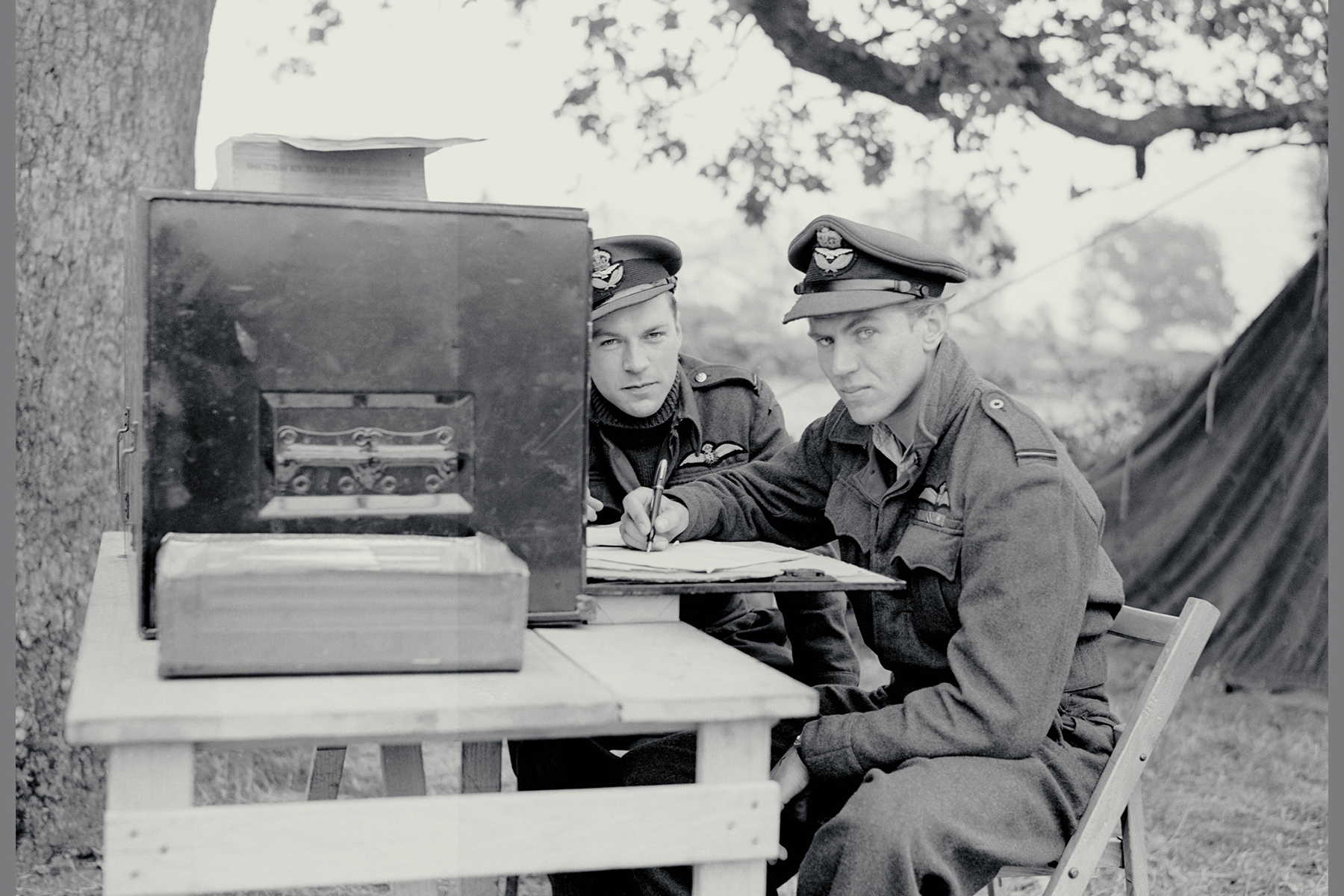 "Flying Officer Bob Middlemiss (left) and Flying Officer Buzz Beurling, of 403 ""Wolf"" Squadron, buy Canadian Victory Bonds at an advanced airfield in England on October 15, 1943. PHOTO: DND Archives, PL-22149"