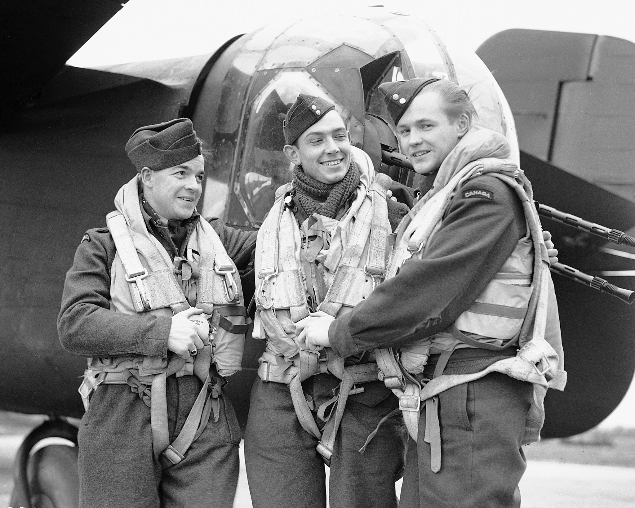 "The original caption of this 434 Squadron photo, taken on February 9, 1944, reads: ""These three airman from the Bluenose Squadron of the RCAF Bomber Group in England are now members of the 'Caterpillar Club' which is limited to those who have bailed out of an aircraft and walked home. It was during a recent attack on Berlin that their aircraft was shot up by flak from the enemy's defences which set the incendiaries on fire in the bomb bay, shot the rudder control away, making the aircraft hard to handle. On the way home they also ran short of petrol and were forced to 'hit the silk'. Shown adjusting parachute harness locks are (left to right) Sergeant Don Tofflemire, rear gunner; Sergeant W.G. ""Bill"" Whitton, mid-upper gunner; and Flight Sergeant Jim Campbell, bomb aimer."" PHOTO: DND Archives, PL-22973"
