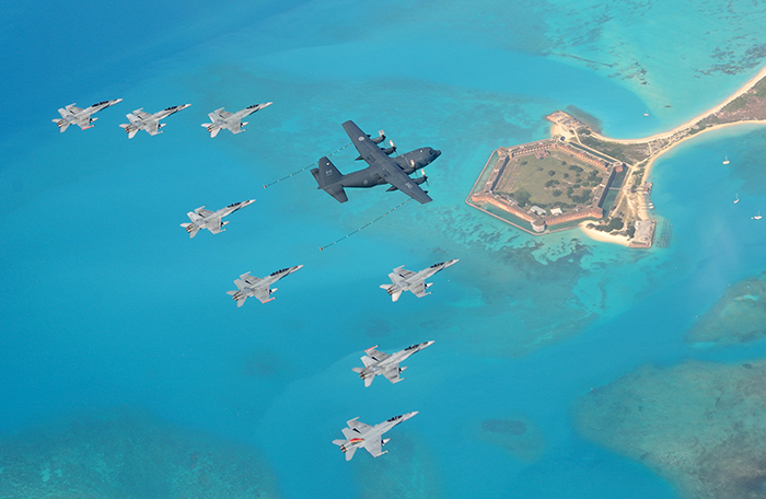 slide - A view from above of a large transport aircraft and eight fighter aircraft flying over an old fort in surrounded by water.