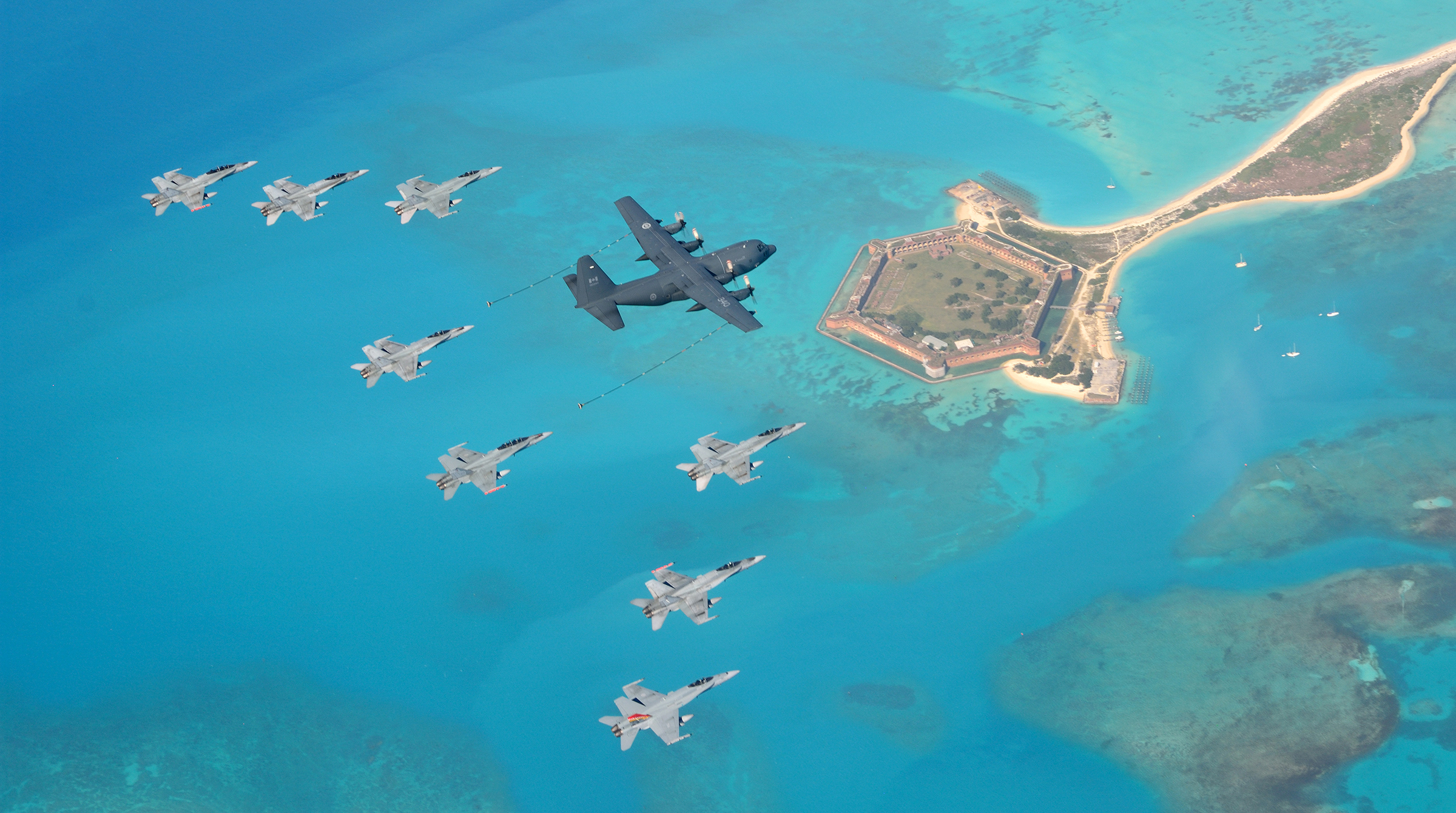A view from above of a large transport aircraft and eight fighter aircraft flying over an old fort in surrounded by water.