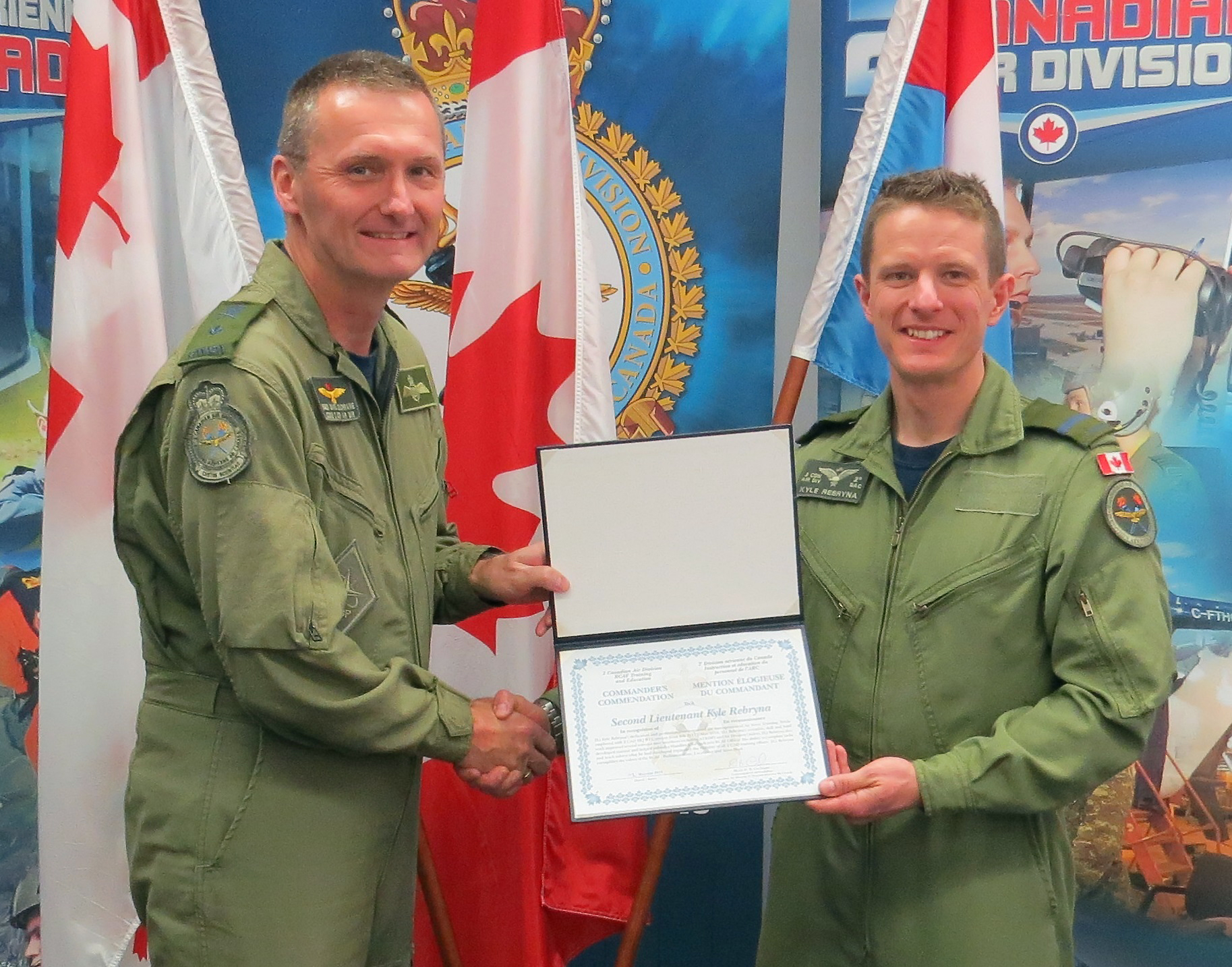 Two men in green flying uniforms hold a certificate in a folder between them.