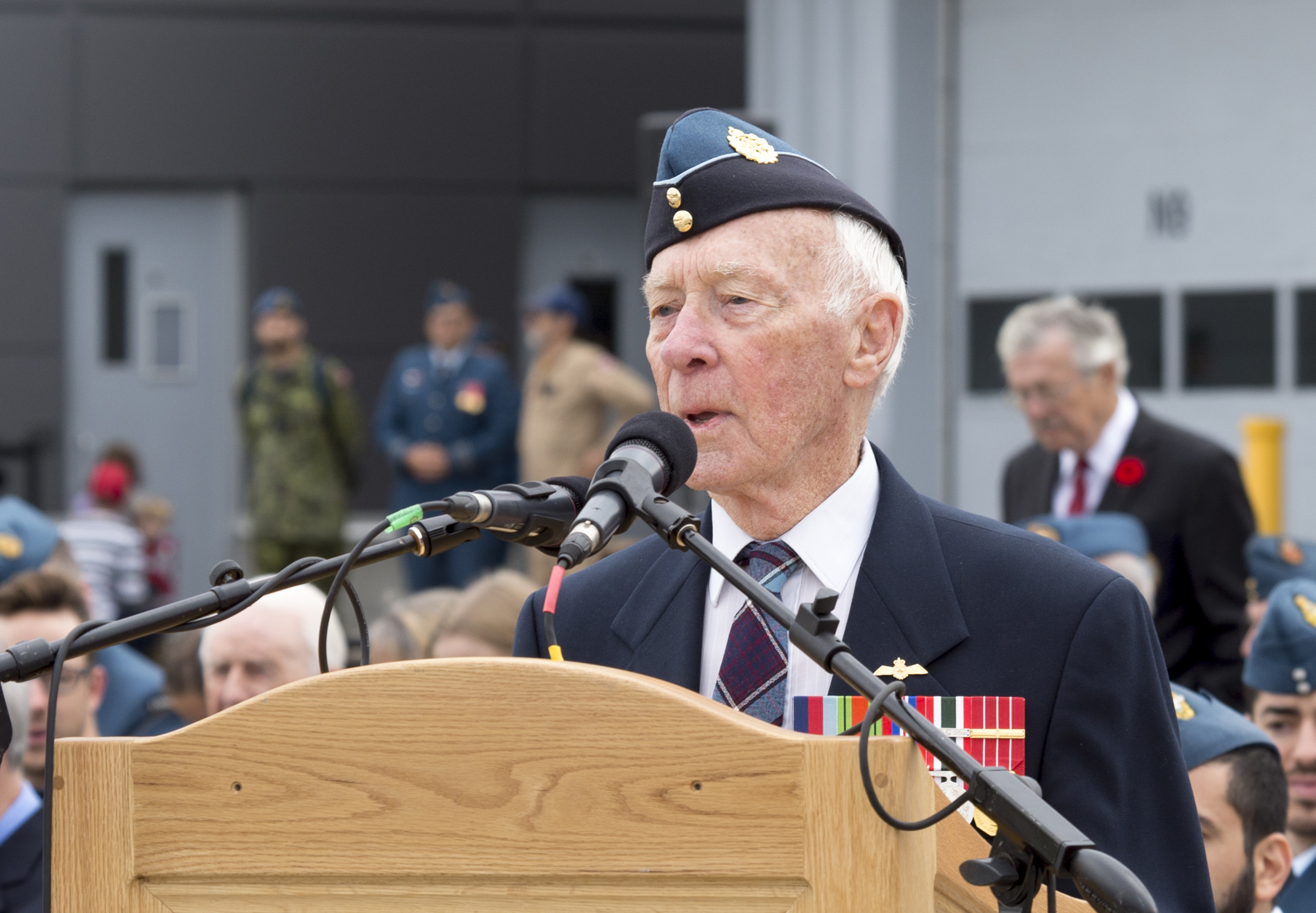 An elderly man, wearing a jacket and tartan tie and a wedge cap, with medals on his jacket, stands behind a podium speaking into microphones.