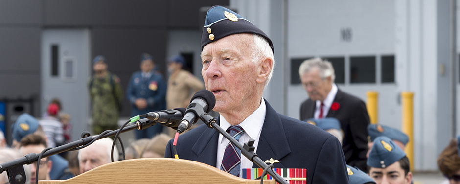 slide - An elderly man, wearing a jacket and tartan tie and a wedge cap, with medals on his jacket, stands behind a podium speaking into microphones.