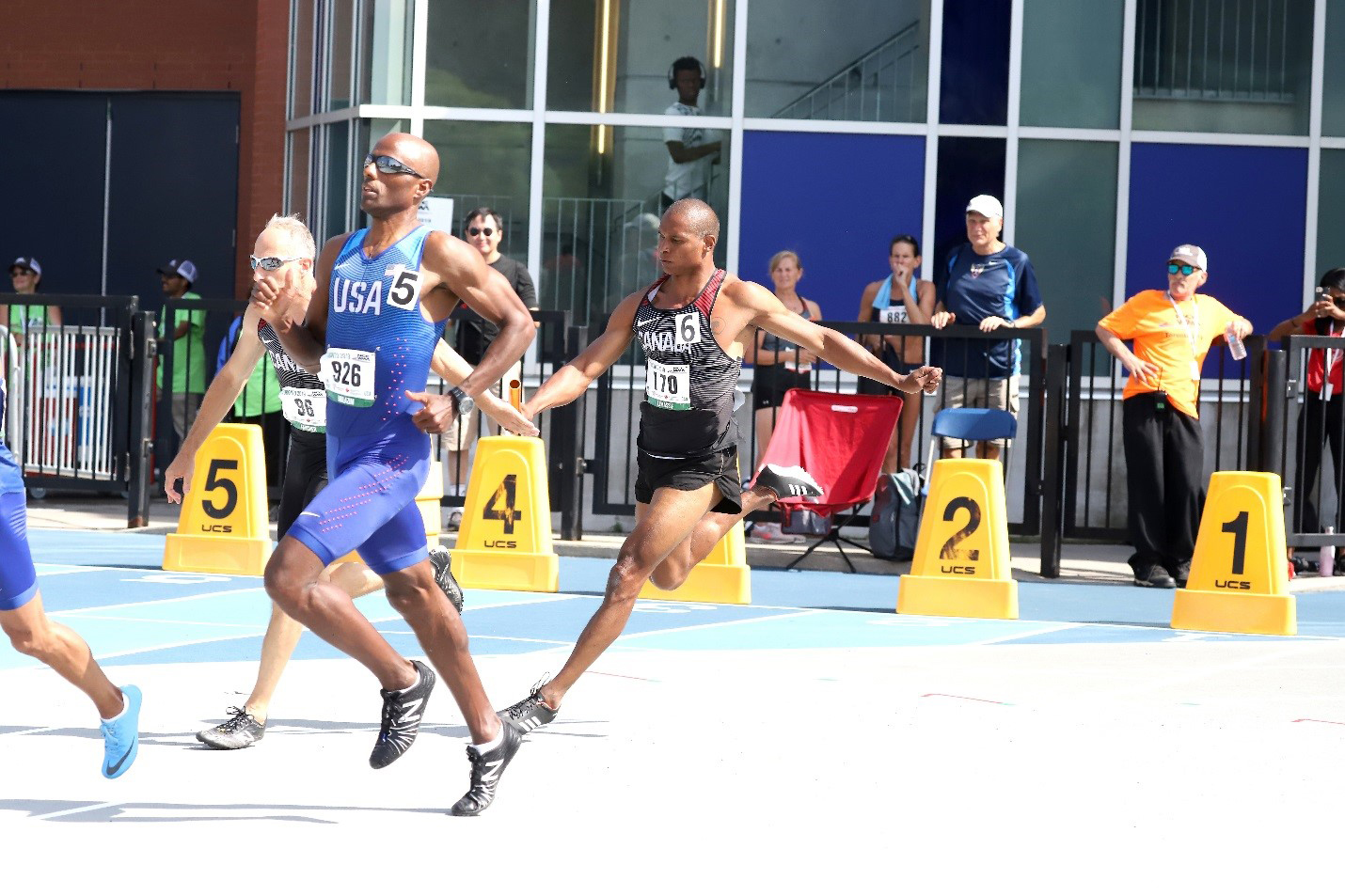On their way to a second-place finish in the 4x100m relay (M55), Major Serge Faucher (second left, back) receives the baton from Christian Lemassif (centre) at the North, Central America and Caribbean Region of World Masters Athletics (NCCWMA) Championships in July 2019. Khalid Mulazim from the US, wearing bib 926, is the fastest M50 400m runner in the world. PHOTO: Submitted