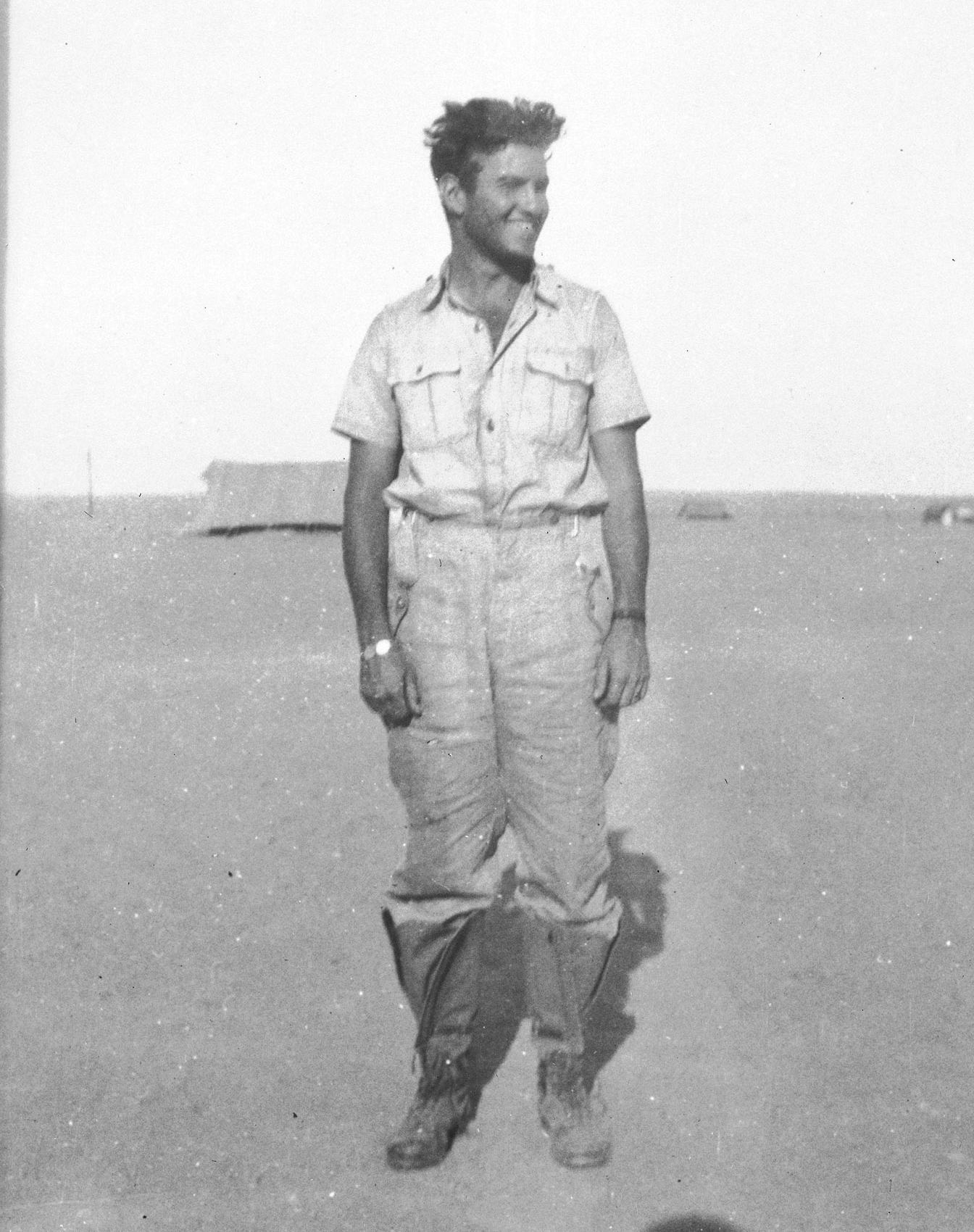 Flight Lieutenant Jack Watts in Tobruk, Libya. He was shot down over the Mediterranean and swam five hours through darkness to safety. He then broke into a German camp—luckily the day after they abandoned the position. He is still wearing the German clothing he found in the camp as he had discarded his own clothing during his long swim. PHOTO:  DND Archives, PL-13674