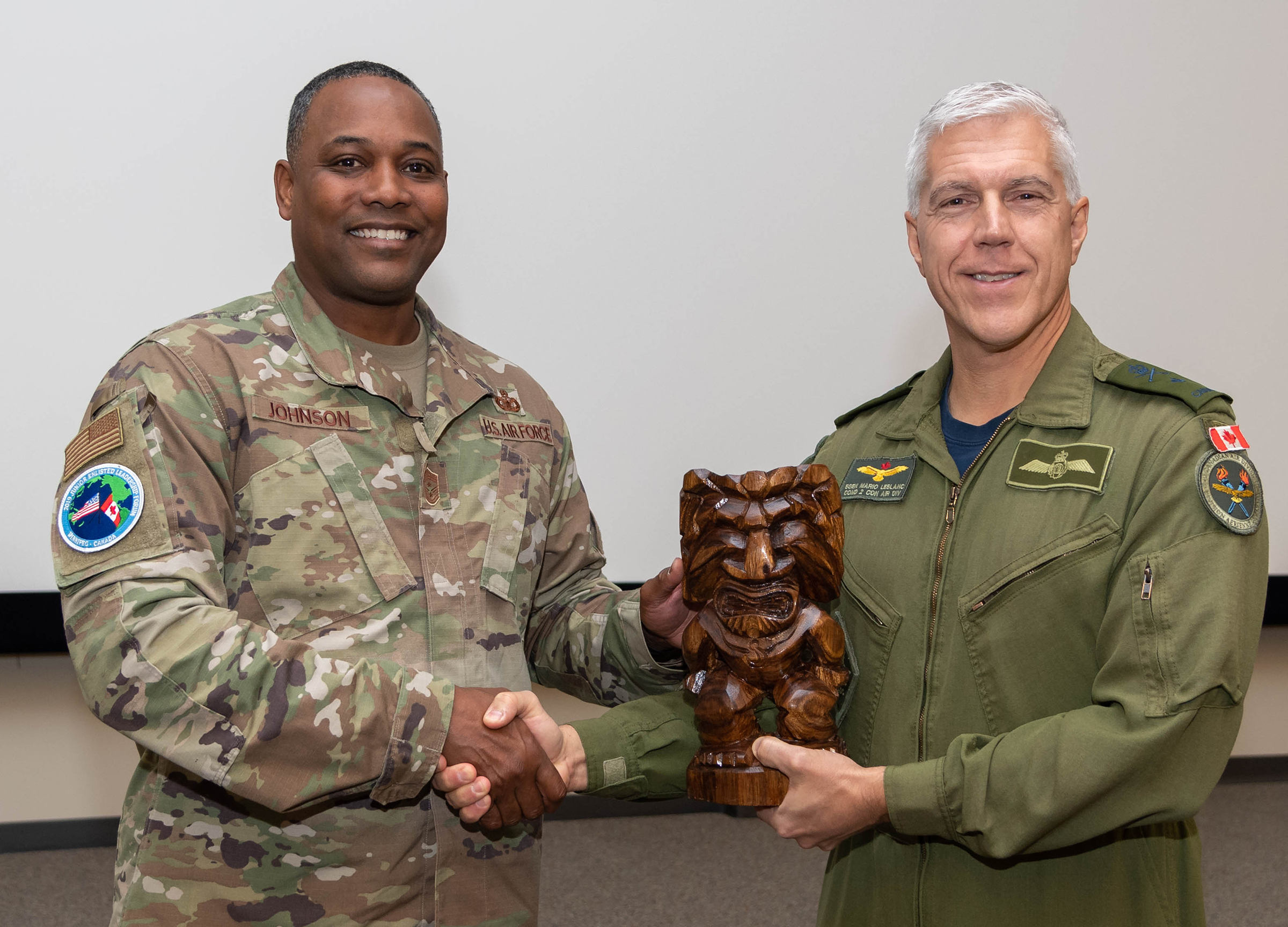 Le brigadier-général Mario Leblanc (à droite), commandant de la 2e Division aérienne du Canada, reçoit un cadeau du Chief Master Sergeant Anthony Johnson, commandant en chef des Pacific Air Forces de la United States Air Force, pendant le Forum de leadership des militaires du rang subalternes, tenu à la 17e Escadre Winnipeg, au Manitoba, du 21 au 25 octobre 2019. PHOTO : Caporal Brian Lindgren, WG2019-0525-013