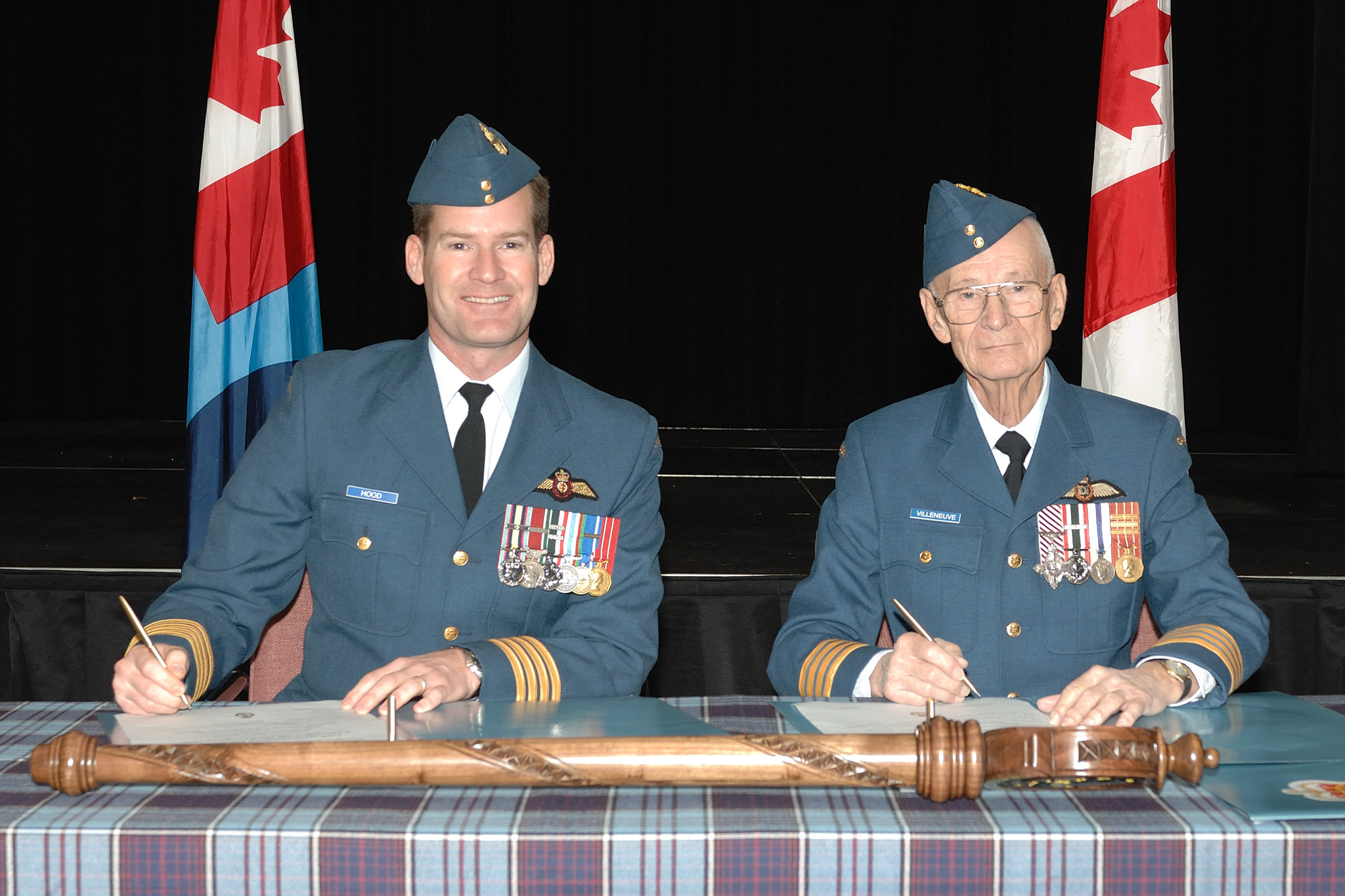 Le 4 décembre 2008, le colonel Mike Hood (à gauche), commandant de la 8e Escadre Trenton, et le lieutenant-colonel (à la retraite) Fern Villeneuve signent les documents officialisant la nomination du lieutenant-colonel Villeneuve comme colonel honoraire du 8e Escadron de maintenance (Air) à Trenton, en Ontario. PHOTO : Soldat Tina Gillies, TN2008-0816-01