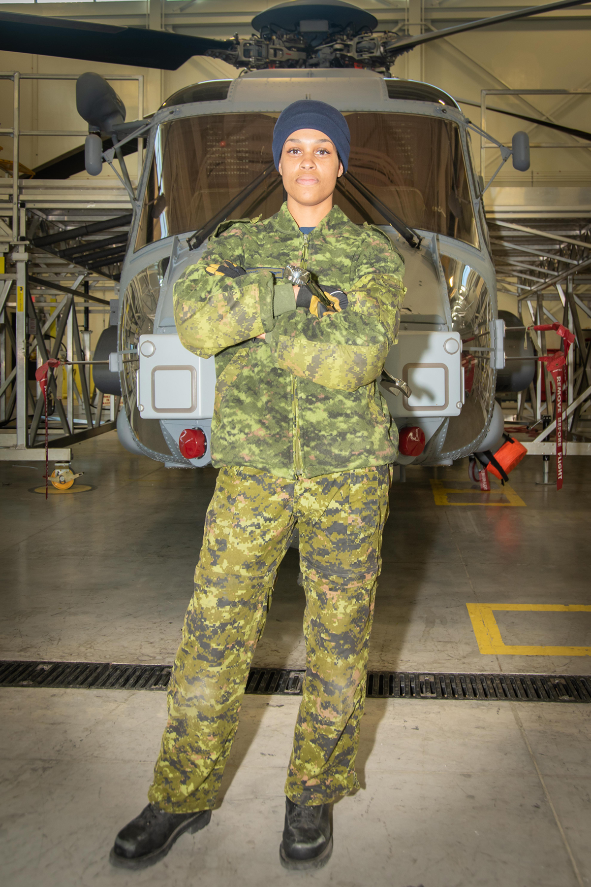 12 Wing member Corporal Caylen Dorrington stands in front of one of the RCAF's new CH-148 Cyclone helicopters. PHOTO: Leading Seaman Brad Upshall