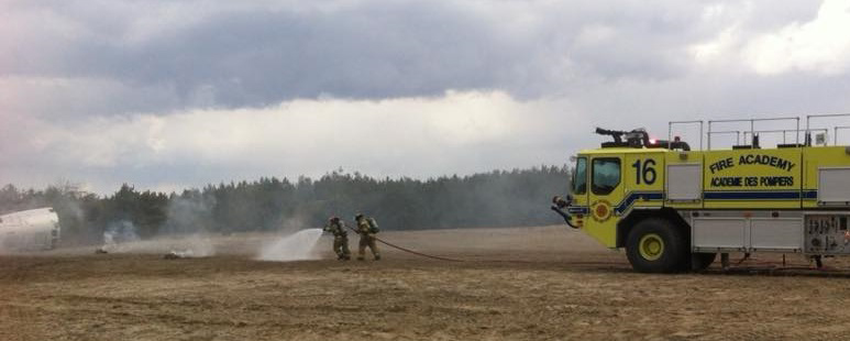In a dirt field, two firefighters in full gear drag a flowing hose from a fire engine toward smoking pieces of metal.