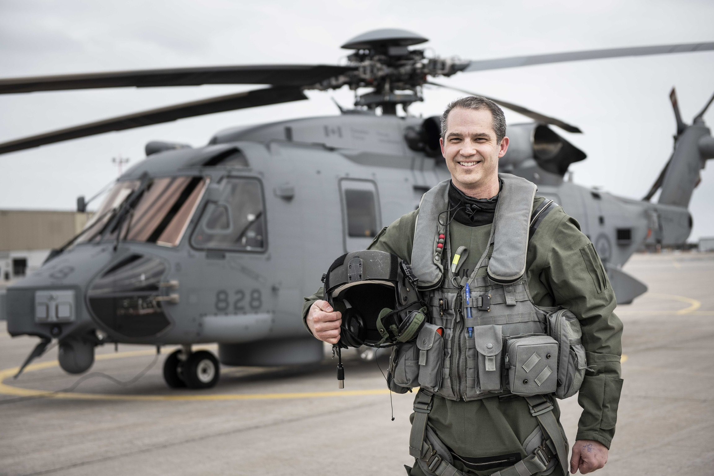 A smiling man in a olive green flight suit holding a pilot's helmet stands in front of a grey helicopter.