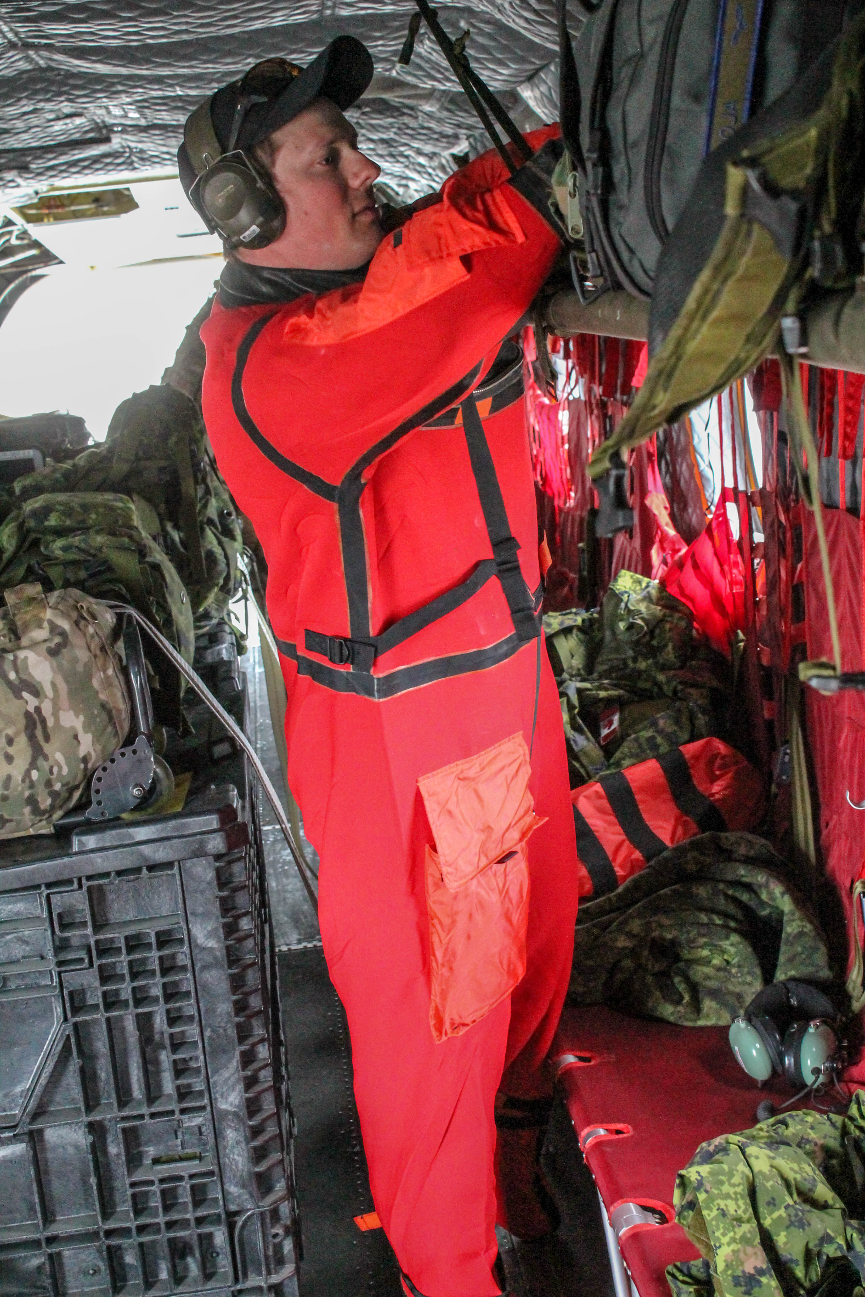 Corporal Christopher Andrew, an Avionics Systems Technician, donning his immersion suit prior to the open water transit. PHOTO: Corporal Justin Critchley