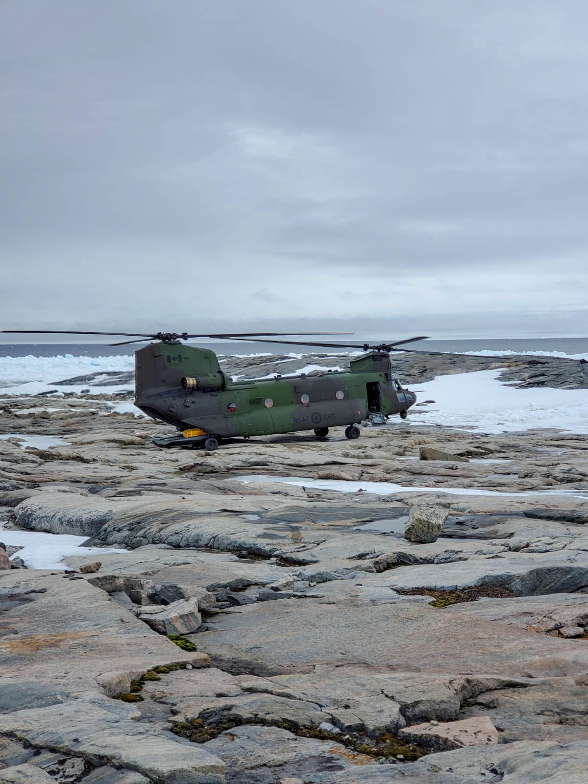 A big green and grey helicopter sits on rocks in an Arctic setting.