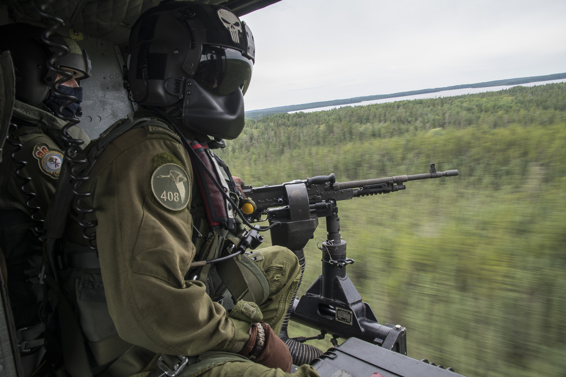 Two men wearing green flight suits and black helmets, one of which mans a machine gun, sit at the open door of a helicopter flying over a wooded area.