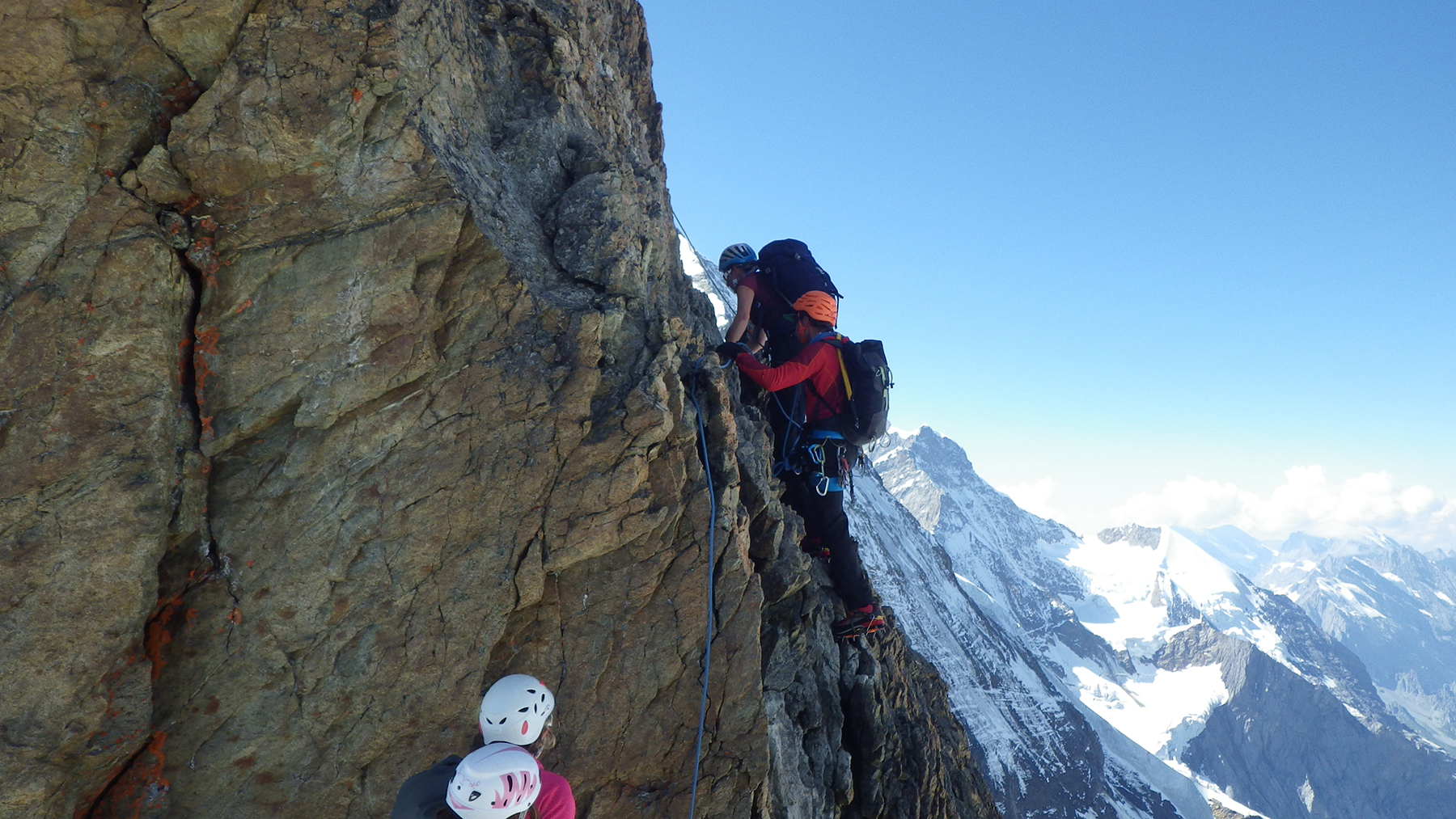 On a traverse on the Eiger on August 28, 2016, just below the summit, Guillaume Omont (in orange) leads, setting up anchors for the team. PHOTO: Captain Antoine Labranche