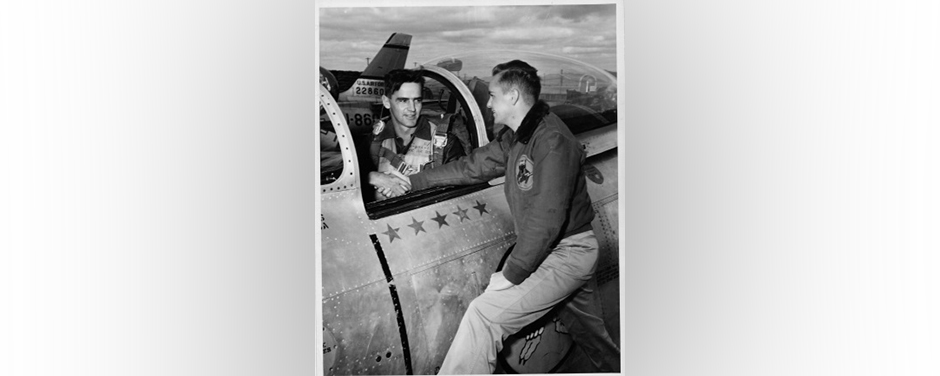 slide - A vintage photo of two men shaking hands, one sitting in the cockpit of an aircraft and the other standing beside it.