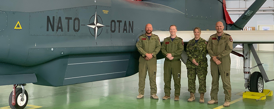 slide - Four people, three men and a woman, wearing military uniforms, stand in front of a grey aircraft.