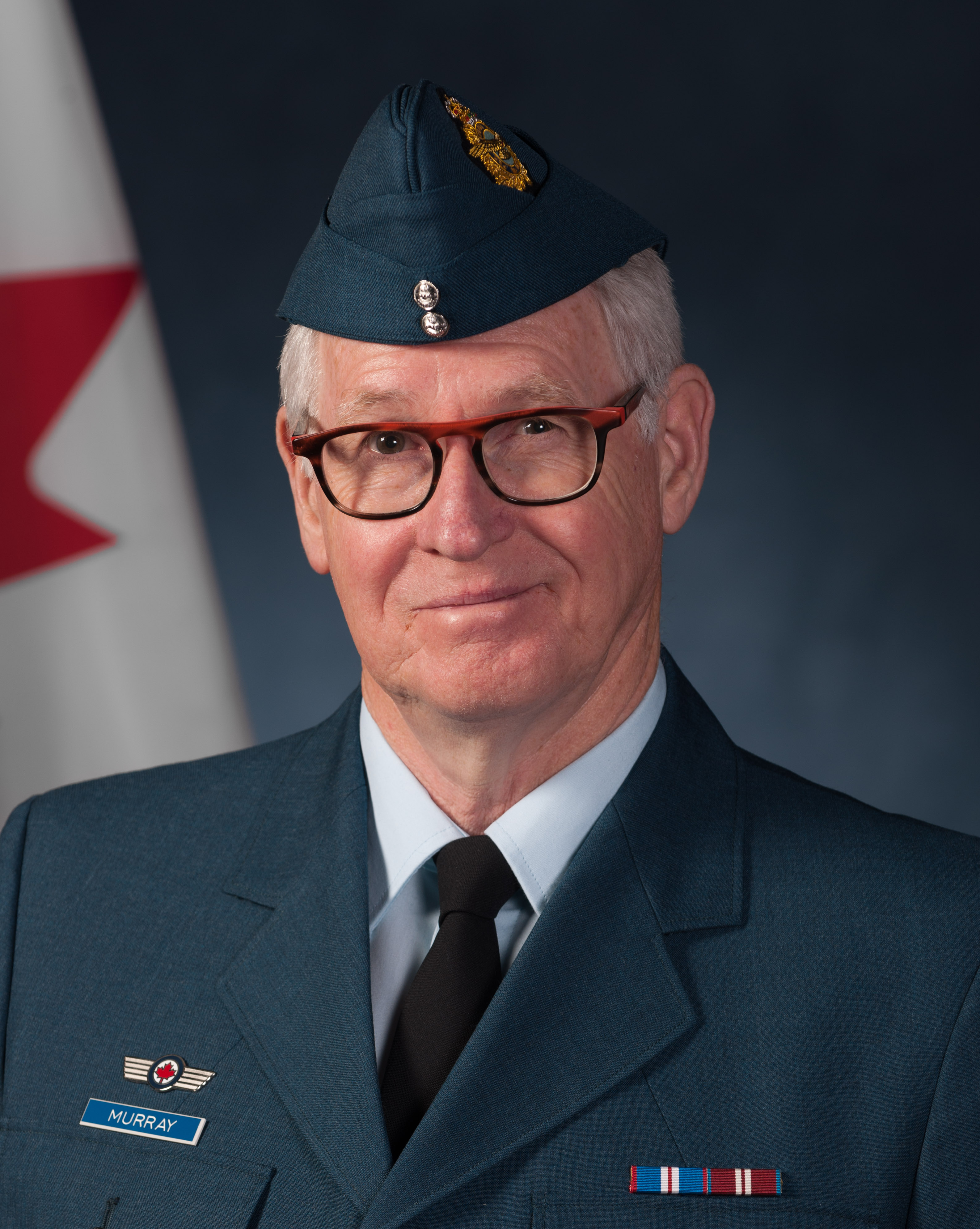 A photo of a man wearing a blue uniform, a wedge hat and glasses.