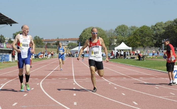 Three men run on an outdoor track during a competition.