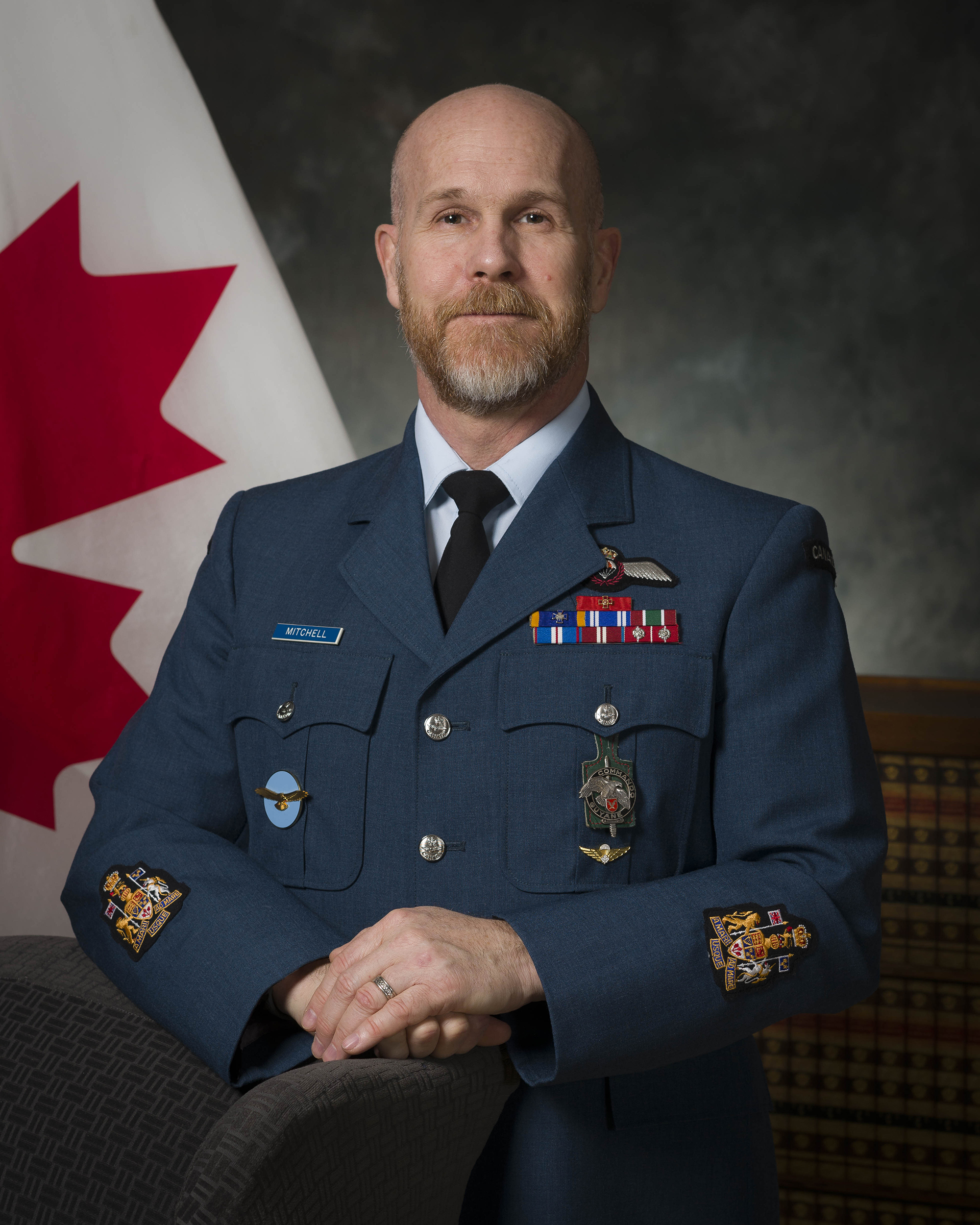A photo of a man wearing a blue military uniform with medals. Behind him is a Canadian flag.