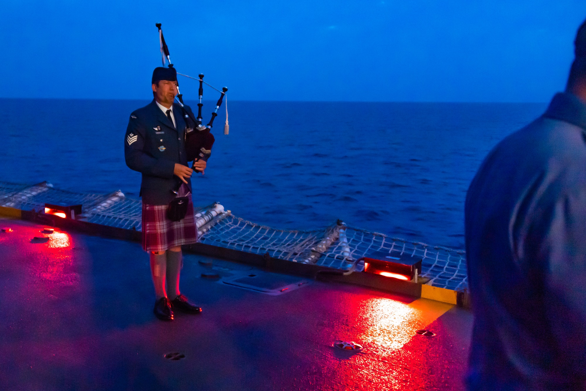 A man plays bagpipes on the deck of a ship in the early morning darkness.