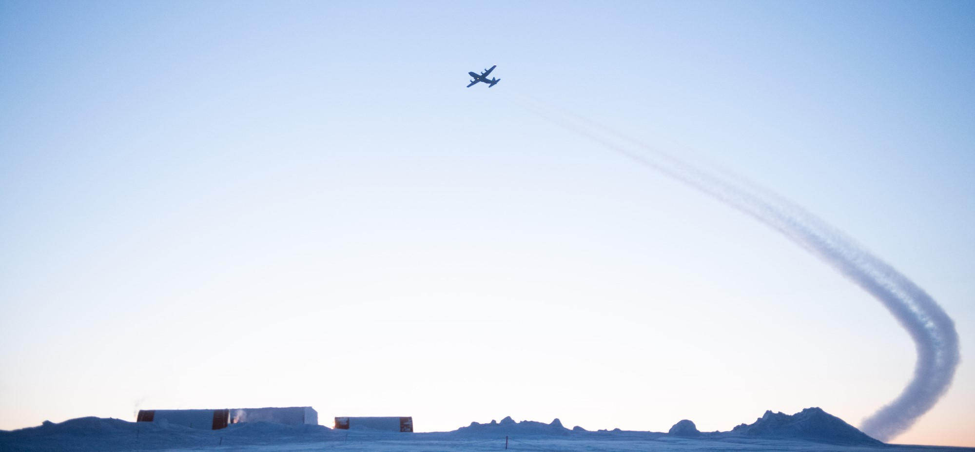 In a photo that shows an Arctic landscape, a big propeller aircraft flies in a blue sky leaving a vapour trail behind it.